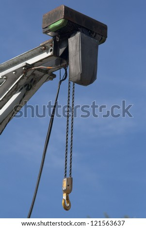A crane in front of blue sky with a motor