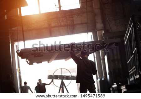 A crane lifts a stove at a factory. Worker controls the lifting process.