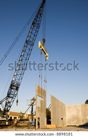 A crane setting a poured concrete two story wall in place