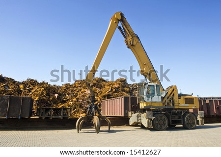 A crane with a huge claw in front of a steel scrap heap