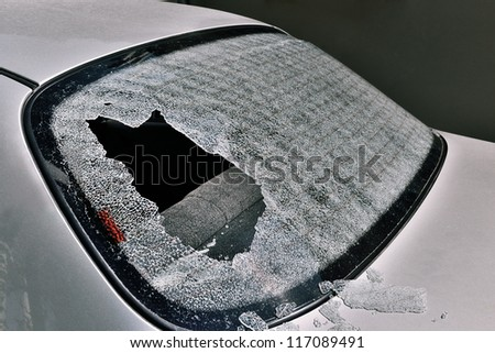 a crashed car heated rear window broken by an accidentally cast stone