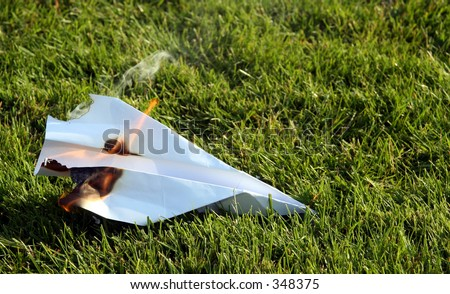 A crashed paper airplane that caught fire on blurred grass background