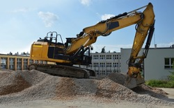 A crawler excavator on a pile of gravel near the school building (construction of a parking lot for cars)