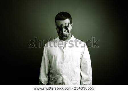 A crazy man dressed with a white gown having his eyes and his mouth covered with black duct tape.
