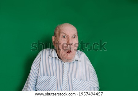 a crazy old man makes faces and grimaces against an isolated green background. chromakey Сток-фото ©