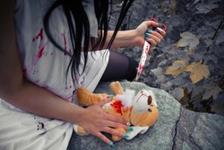 A crazy psycho girl stabbing a fluffy toy with a bloody knife
