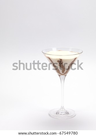 a cream and chocolate pudding served in a martini glass on a white background