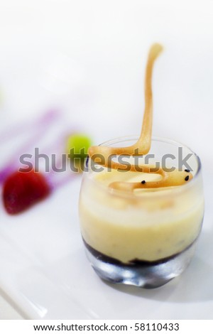 A creamy dessert with crushed pistachio nuts and chocolate ganache, served with fresh caramel fruits