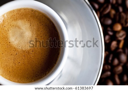 A creamy espresso on a bed of coffe beans