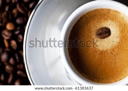 A creamy espresso with a coffe bean