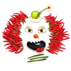 A creative food concept demonstrating a creepy halloween clown with the help of chilli pepper and other vegetables.