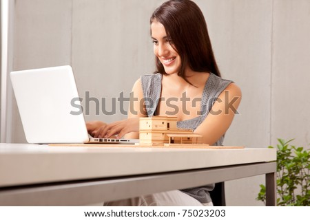A creative professional woman working at a desk with a laptop and house model