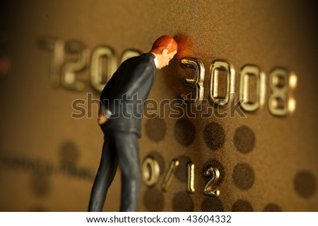 A credit card with a figure of a man leaning on it and worrying.