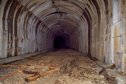 A creepy, abandoned,spooky railroad tunnel, with no light at the end of the tunnel.  There is a pile of debris, no tracks and several water stains running down the sides of the tunnel.