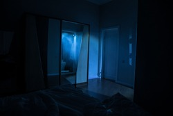 A creepy bedroom scenery, Silhouette of scary person standing reflected in mirror with mist and toned light. Horror Halloween concept