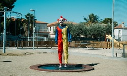 a creepy clown, wearing a colorful yellow, red and blue costume, is bouncing on a trampoline in an outdoor public playground