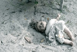 A creepy doll lies on an old abandoned playground