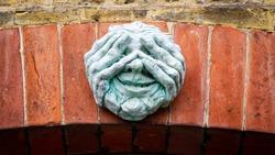 A creepy Peeping Tom on a brick lintel