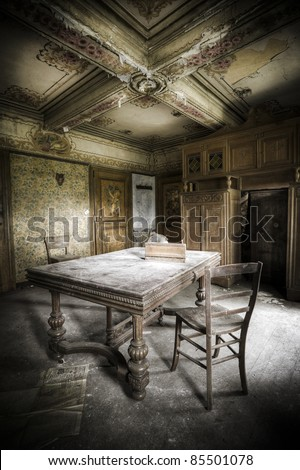 A creepy scenery, this old table and chair waiting for a person to take a seat.
