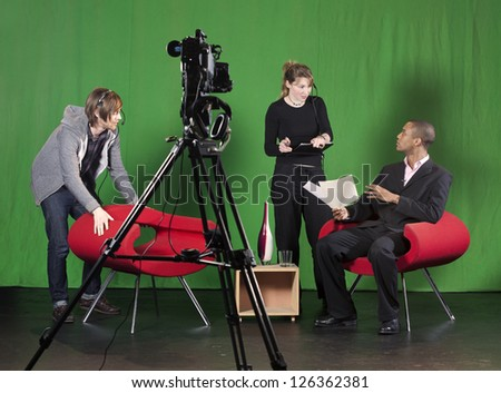 A crew member arranges furniture whilst the floor manager talks to the presenter on a TV studio set. TV camera on a tripod out-of-focus in the foreground.
