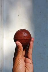 A cricket ball on hand,raver cricket ball