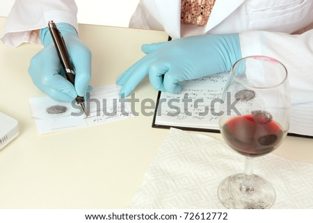 A crime scene forensic scientist obtains fingerprints from a glass using latent powder and tape and then writes down details.  Details are fictitious.