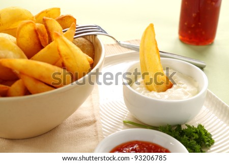 A crisp potato wedge dunked in a bowl of sour cream.
