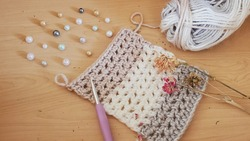 A crocheted scarf pattern in progress, made in a neutral toned, chunky, self striping yarn, and posed with pearls, dried flowers, and a lavendar crochet hook.