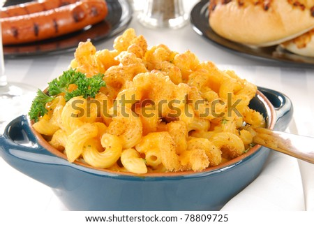 A crock of baked gourmet macaroni and cheese with rolls and hot dogs