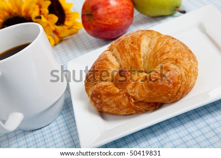 A croissant on a white plate with coffee and apples on a blue gingham tablecloth with sunflowers