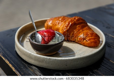 A croissant with ice-cream and strawberry jam on a plate, on a wooden table of a cafe terrace. Minsk, Belarus. Natural light. Selective focus. #683035348