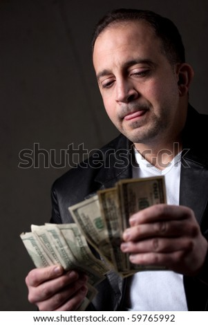 A crooked looking man counting a handful of one hundred dollar bills. Shallow depth of field with focus on the face.