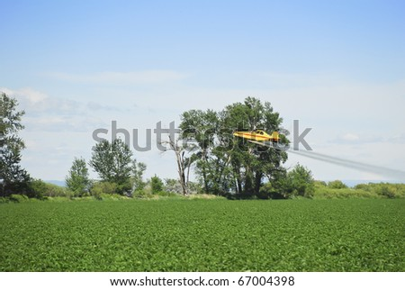 A crop duster applies chemicals to a field