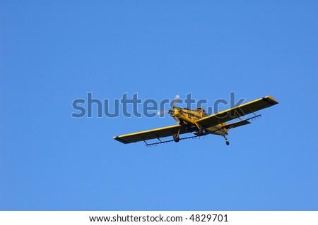 A crop dusting plane in flight.