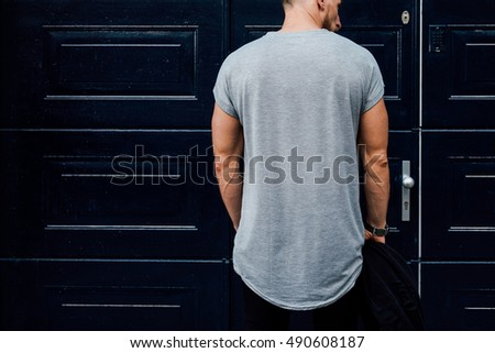 A cropped photo of a bearded man wearing a blank gray t-shirt while standing with his back to the camera beside the dark blue entrance doors on a street. Empty place for the logo or design. Mock up. Stock fotó ©