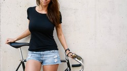A cropped photo of a girl with long brown hair wearing a blank black t-shirt standing on a concrete wall background on a street. Empty space for text or design.
