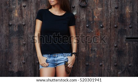 fe1d8519c6f4f A cropped photo of a young woman wearing black blank t-shirt and blue jeans