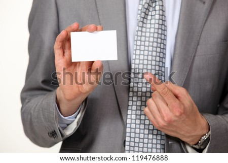 A cropped picture of a businessman showing his card.