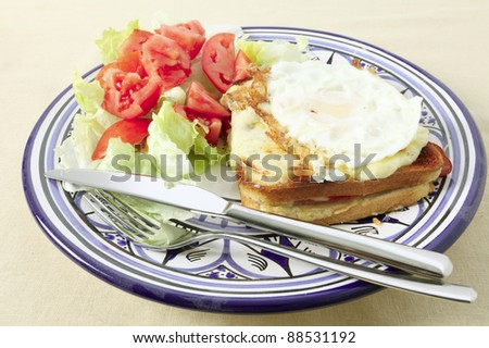 A croque madame - toasted cheese and ham sandwich topped with bechamel sauce and a fried egg - with a tomato and lettuce salad