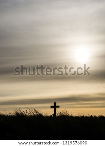 A cross and long grasses silhouetted against a wintry afternoon sky. The sun is just breaking through the clouds. Taken on Llanddwyn Island, Anglesey, North Wales #1319576090