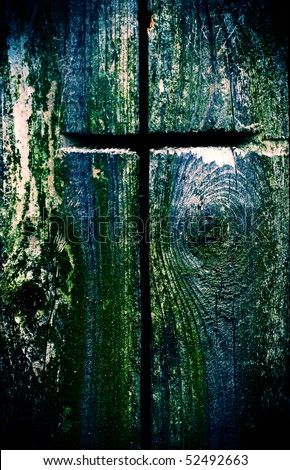 A cross carved into old wood in a cross processed style.