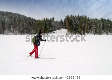A cross country skier out on a refreshing trip over a frozen lake.