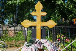 A cross on a fresh grave in a Christian cemetery. Close-up. Everlasting memory.