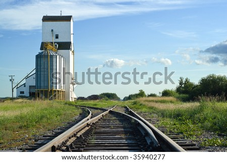 A crossroad section of the railroad tracks with one side going to a grain elevator and the other going straight and disappearing in the distance