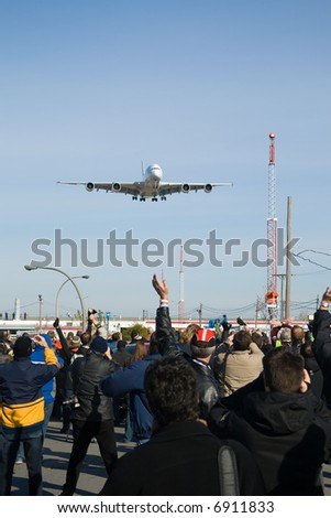 A crowd acclaims the first Airbus A380 to land in Montreal Airport.