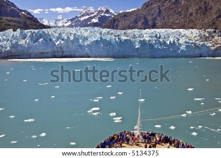 A crowd gathers at the bow of a cruise ship as it approaches a glacier on the  Alaska coast in Glacier Bay.