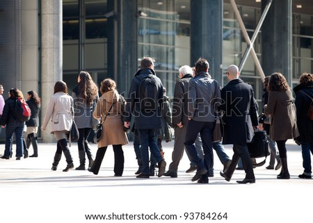 A crowd moving against a background of an urban landscape. - stock photo