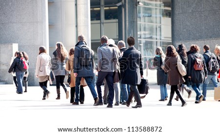A crowd moving against a background of an urban landscape. Young people.