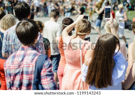 a crowd of citizens. many citizens on a city street, view from behind, blur