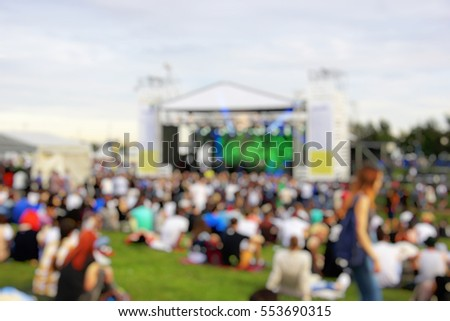 A crowd of people at a concert in the park. Near the scene. Blurred background - Shutterstock ID 553690315